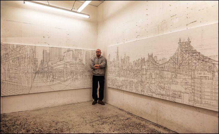 Nathan Walsh vor zwei seiner Zeichnungen